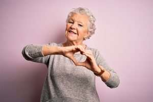 Senior beautiful woman wearing casual t-shirt standing over isolated pink background smiling in love doing heart symbol shape with hands. Romantic concept.