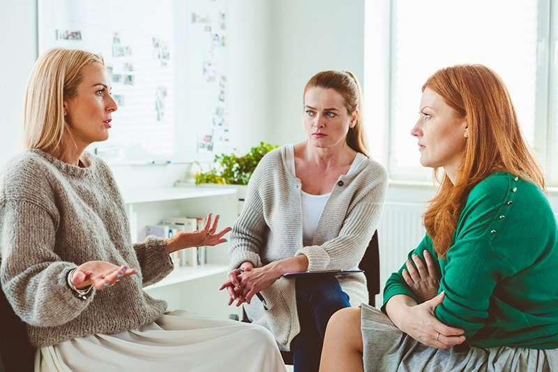 Women discussing problems with therapist at center